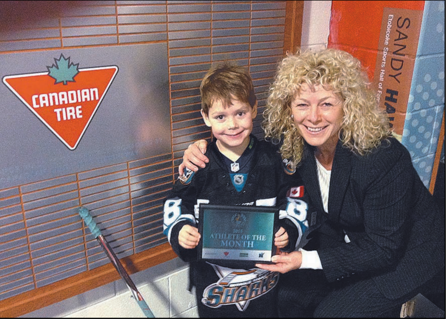 Jack Wright, 6, receives his Athlete of the Month plaque from Etobicoke Sports Hall of Fame Chair Joanne Noble.